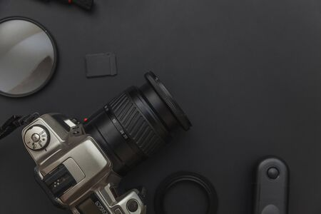 Photographer workplace with dslr camera system, camera cleaning kit, lens and camera accessory on dark black table background. Hobby travel photography concept. Flat lay top view copy space Zdjęcie Seryjne
