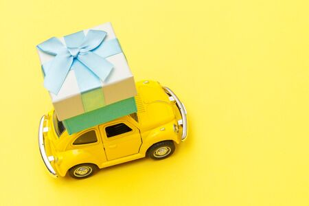 Simply design yellow vintage retro toy car delivering gift box on roof isolated on trendy yellow background. Christmas New Year birthday Valentines day celebration present romantic concept.