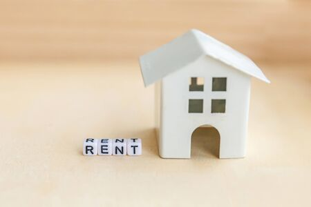 Miniature toy model house with inscription RENT letters word on wooden backdrop. Eco Village abstract environmental background. Real estate mortgage property insurance sweet home ecology rent concept