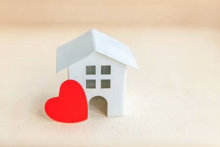 Miniature toy model house with red heart on wooden backdrop. Eco Village, abstract environmental background. Real estate mortgage property insurance sweet dream home ecology concept Фото со стока - 137762089
