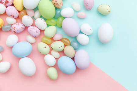 Happy Easter concept. Preparation for holiday. Easter candy chocolate eggs and jellybean sweets isolated on trendy pastel blue pink background. Simple minimalism flat lay top view copy space
