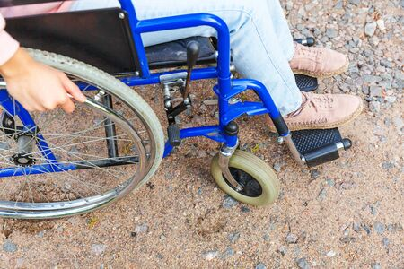 Legs feet handicap woman in wheelchair wheel on road in hospital park waiting for patient services. Unrecognizable paralyzed girl in invalid chair for disabled people outdoors. Rehabilitation concept