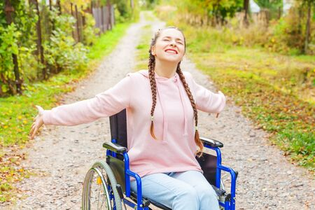 Young happy handicap woman in wheelchair on road in hospital park enjoying freedom. Paralyzed girl in invalid chair for disabled people outdoor in nature. Rehabilitation concept Zdjęcie Seryjne - 138520086