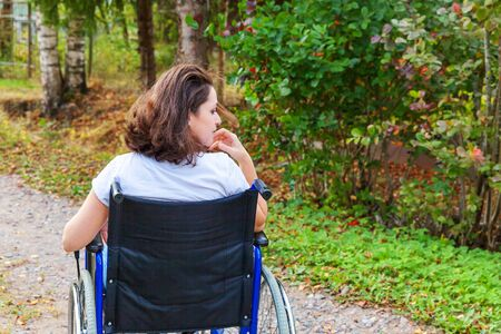 Young happy handicap woman in wheelchair on road in hospital park enjoying freedom. Paralyzed girl in invalid chair for disabled people outdoor in nature. Rehabilitation concept