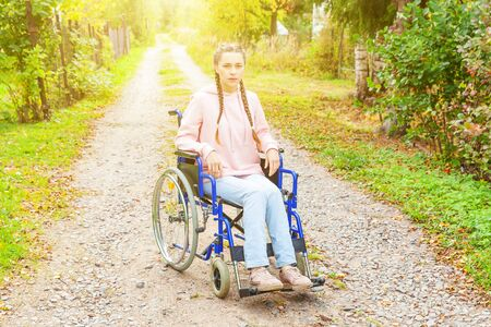 Young happy handicap woman in wheelchair on road in hospital park waiting for patient services. Paralyzed girl in invalid chair for disabled people outdoor in nature. Rehabilitation concept Zdjęcie Seryjne - 138520471