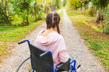 Young happy handicap woman in wheelchair on road in hospital park waiting for patient services. Paralyzed girl in invalid chair for disabled people outdoor in nature. Rehabilitation concept