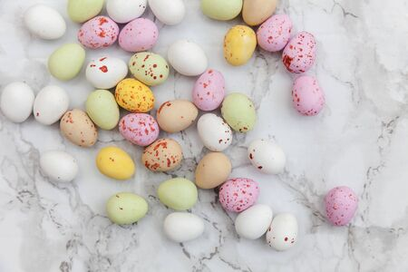 Happy Easter concept. Preparation for holiday. Easter pastel candy chocolate eggs sweets on trendy gray marble background. Simple minimalism flat lay top view copy space Zdjęcie Seryjne