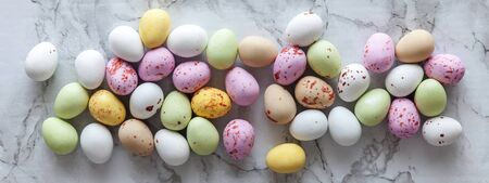 Happy Easter concept. Preparation for holiday. Easter pastel candy chocolate eggs sweets on trendy gray marble background. Simple minimalism flat lay top view copy space. Banner