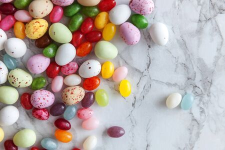 Happy Easter concept. Preparation for holiday. Easter candy chocolate eggs and jellybean sweets on trendy gray marble background. Simple minimalism flat lay top view copy space