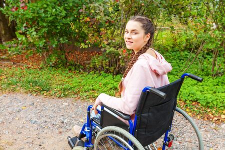 Young happy handicap woman in wheelchair on road in hospital park waiting for patient services. Paralyzed girl in invalid chair for disabled people outdoor in nature. Rehabilitation concept Zdjęcie Seryjne - 138520119