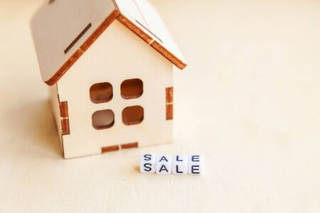 Miniature toy model house with inscription SALE letters word on wooden backdrop. Eco Village abstract environmental background. Real estate mortgage property insurance sweet home ecology rent concept Фото со стока - 137826453