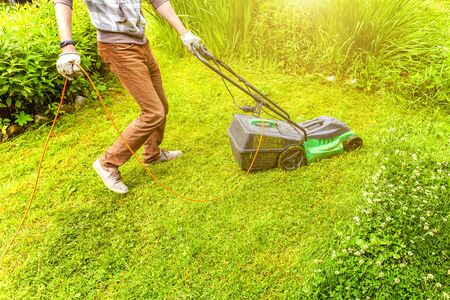 Man cutting green grass with lawn mower in backyard. Gardening country lifestyle background. Beautiful view on fresh green grass lawn in sunlight, garden landscape in spring or summer season Banque d'images - 137826667