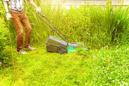 Man cutting green grass with lawn mower in backyard. Gardening country lifestyle background. Beautiful view on fresh green grass lawn in sunlight, garden landscape in spring or summer season Banque d'images - 137827174