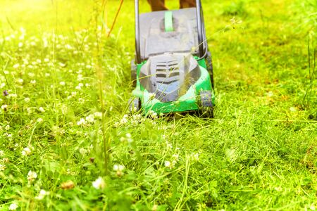 Człowiek cięcie zielonej trawy z kosiarki w podwórku. Ogrodnictwo tło stylu życia kraju. Piękny widok na świeży zielony trawnik w słońcu, ogrodowy krajobraz w sezonie wiosennym lub letnim