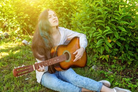 Young hipster woman sitting in grass and playing guitar on park or garden background. Teen girl learning to play song and writing music. Hobby, lifestyle, relax, Instrument, leisure, education concept
