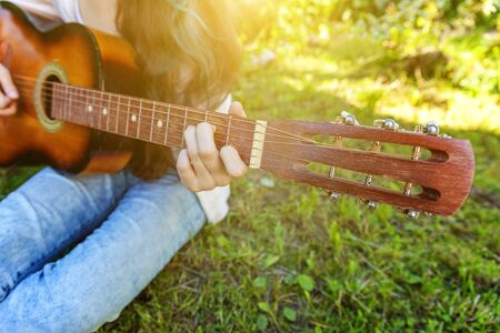 Closeup of woman hands playing acoustic guitar on park or garden background. Teen girl learning to play song and writing music. Hobby, lifestyle, relax, Instrument, leisure, education concept Banque d'images - 138542962