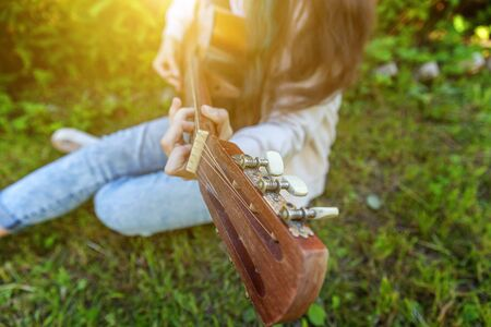 Closeup of woman hands playing acoustic guitar on park or garden background. Teen girl learning to play song and writing music. Hobby, lifestyle, relax, Instrument, leisure, education concept Banque d'images - 138542961
