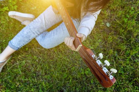 Closeup of woman hands playing acoustic guitar on park or garden background. Teen girl learning to play song and writing music. Hobby, lifestyle, relax, Instrument, leisure, education concept Banque d'images - 138542915