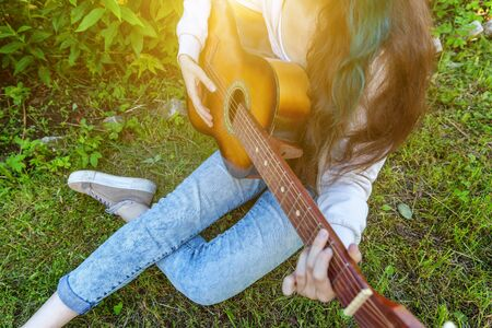 Young hipster woman sitting in grass and playing guitar on park or garden background. Teen girl learning to play song and writing music. Hobby, lifestyle, relax, Instrument, leisure, education concept Banque d'images - 138543150