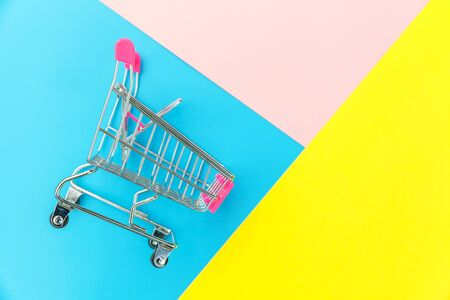 Small supermarket grocery push cart for shopping toy with wheels isolated on blue yellow pink pastel colorful trendy geometric background Copy space. Sale buy mall market shop consumer concept