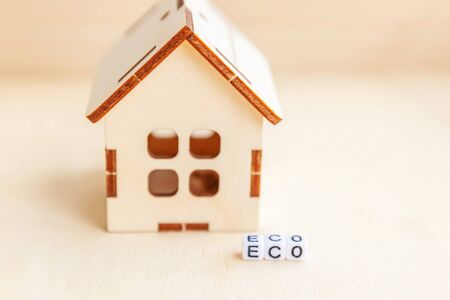 Miniature toy model house with inscription ECO letters word on wooden backdrop. Eco Village abstract environmental background. Ecology zero waste social responsibility recycle bio home concept