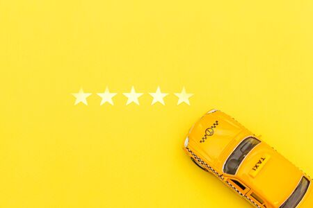 Yellow toy car Taxi Cab and 5 stars rating isolated on yellow background. Smartphone application of taxi service for online searching calling and booking cab concept. Taxi symbol. Copy space