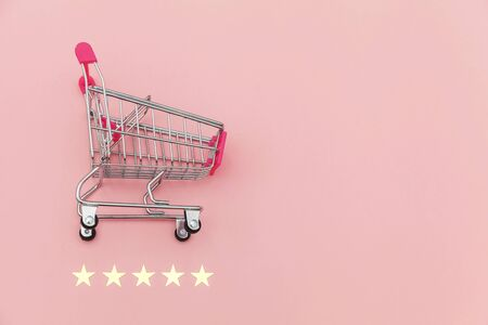 Small supermarket grocery push cart for shopping toy with wheels and 5 stars rating isolated on pastel pink background. Retail consumer buying online assessment and review concept Reklamní fotografie