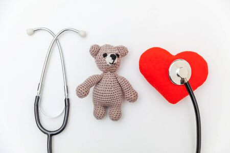 Simply minimal design toy bear red heart and medicine equipment stethoscope isolated on white background. Health care children doctor concept. Pediatrician symbol. Flat lay top view copy space Reklamní fotografie