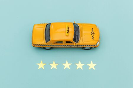 Yellow toy car Taxi Cab and 5 stars rating isolated on blue background. Smartphone application of taxi service for online searching calling and booking cab concept. Taxi symbol. Copy space