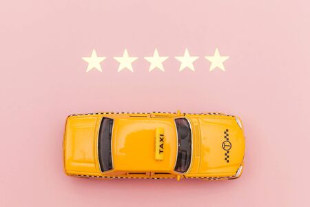 Yellow toy car Taxi Cab and 5 stars rating isolated on pink background. Smartphone application of taxi service for online searching calling and booking cab concept. Taxi symbol. Copy space