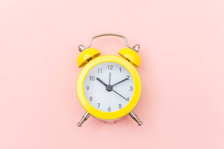 Ringing twin bell vintage classic alarm clock Isolated on pink colourful trendy pastel background. Rest hours time of life good morning night wake up awake concept. Flat lay top view copy space