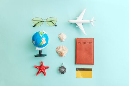Vacation travel adventure trip concept. Minimal simple flat lay with plane passport sunglasses globe gold credit card and shell on blue pastel colorful trendy background. Tourist essentials