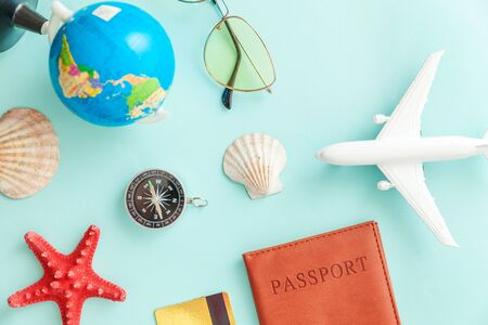 Vacation travel adventure trip concept. Minimal simple flat lay with plane passport sunglasses globe gold credit card and shell on blue pastel colourful trendy background. Tourist essentials
