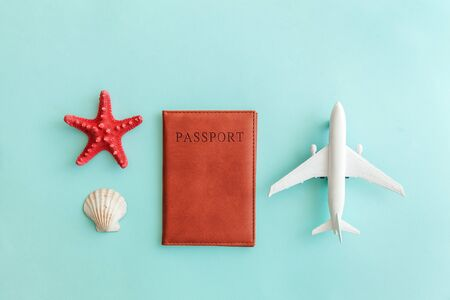 Vacation travel adventure trip concept. Minimal simple flat lay with plane passport and shell on blue pastel colourful trendy background. Tourist essentials Copy space