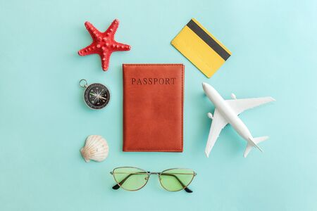 Vacation travel adventure trip concept. Minimal simple flat lay with plane passport sunglasses compass gold credit card shell on blue pastel colourful trendy background. Tourist essentials Copy space