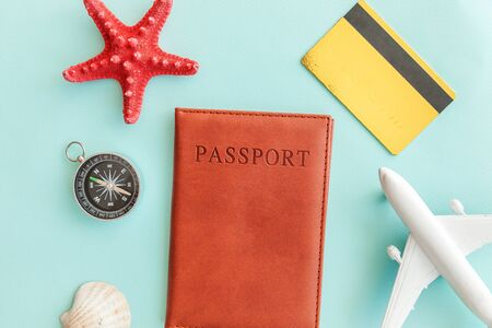 Vacation travel adventure trip concept. Minimal simple flat lay with plane passport gold credit card and shell on blue pastel colourful trendy background. Tourist essentials Copy space