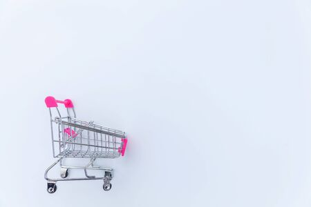 Small supermarket grocery push cart for shopping toy with wheels isolated on white background. Sale buy mall market shop consumer concept. Copy space
