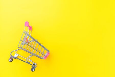 Small supermarket grocery push cart for shopping toy with wheels isolated on yellow colourful trendy modern fashion background. Sale buy mall market shop consumer concept. Copy space