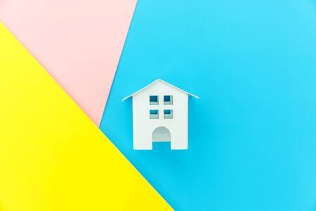 Simply design with miniature white toy house isolated on blue yellow pink pastel colorful trendy geometric background Mortgage property insurance dream home concept. Flat lay top view copy space