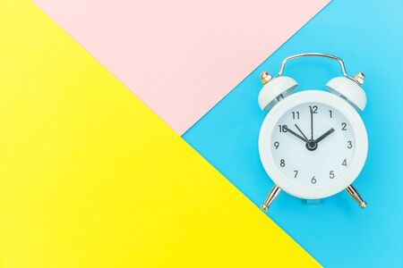 Ringing twin bell classic alarm clock isolated on blue yellow pink pastel colorful geometric background. Rest hours time of life good morning night wake up awake concept. Flat lay top view copy space Foto de archivo - 139861943