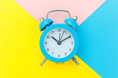 Ringing twin bell classic alarm clock isolated on blue yellow pink pastel colorful geometric background. Rest hours time of life good morning night wake up awake concept. Flat lay top view copy space Foto de archivo - 139861923