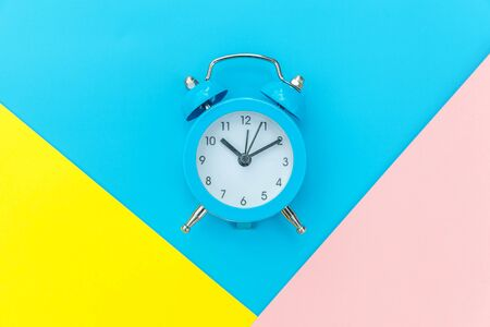 Ringing twin bell classic alarm clock isolated on blue yellow pink pastel colorful geometric background. Rest hours time of life good morning night wake up awake concept. Flat lay top view copy space Foto de archivo - 139861929