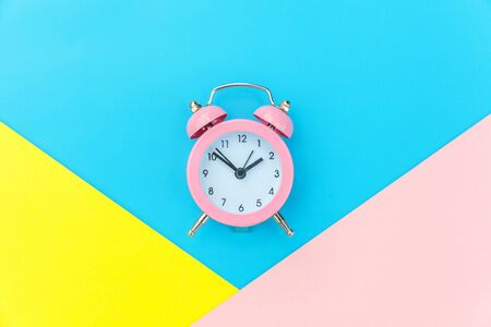 Ringing twin bell classic alarm clock isolated on blue yellow pink pastel colorful geometric background. Rest hours time of life good morning night wake up awake concept. Flat lay top view copy space Foto de archivo - 139862031