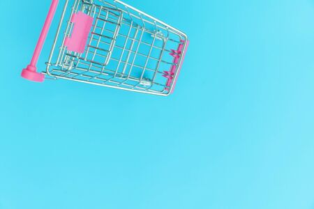 Small supermarket grocery push cart for shopping toy with wheels isolated on blue pastel colorful trendy background Copy space. Sale buy mall market shop consumer concept