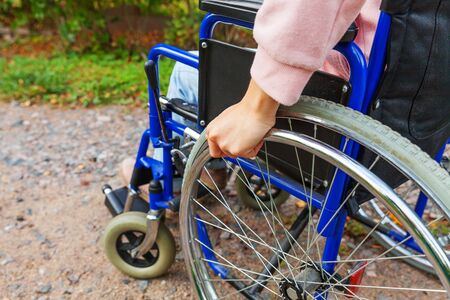 Hand handicap woman in wheelchair wheel on road in hospital park waiting for patient services. Unrecognizable paralyzed girl in invalid chair for disabled people outdoors. Rehabilitation concept
