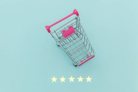 Small supermarket grocery push cart for shopping toy with wheels and 5 stars rating isolated on pastel blue background. Retail consumer buying online assessment and review concept