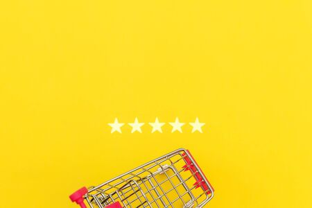 Small supermarket grocery push cart for shopping toy with wheels and 5 stars rating isolated on yellow background. Retail consumer buying online assessment and review concept