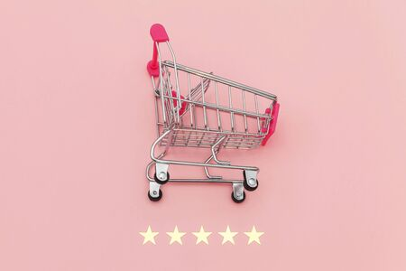 Small supermarket grocery push cart for shopping toy with wheels and 5 stars rating isolated on pastel pink background. Retail consumer buying online assessment and review concept 스톡 콘텐츠