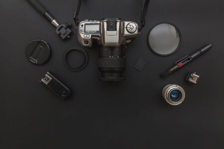 Photographer workplace with dslr camera system, camera cleaning kit, lens and camera accessory on dark black table background. Hobby travel photography concept. Flat lay top view copy space Banco de Imagens