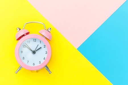 Ringing twin bell classic alarm clock isolated on blue yellow pink pastel colorful geometric background. Rest hours time of life good morning night wake up awake concept. Flat lay top view copy space